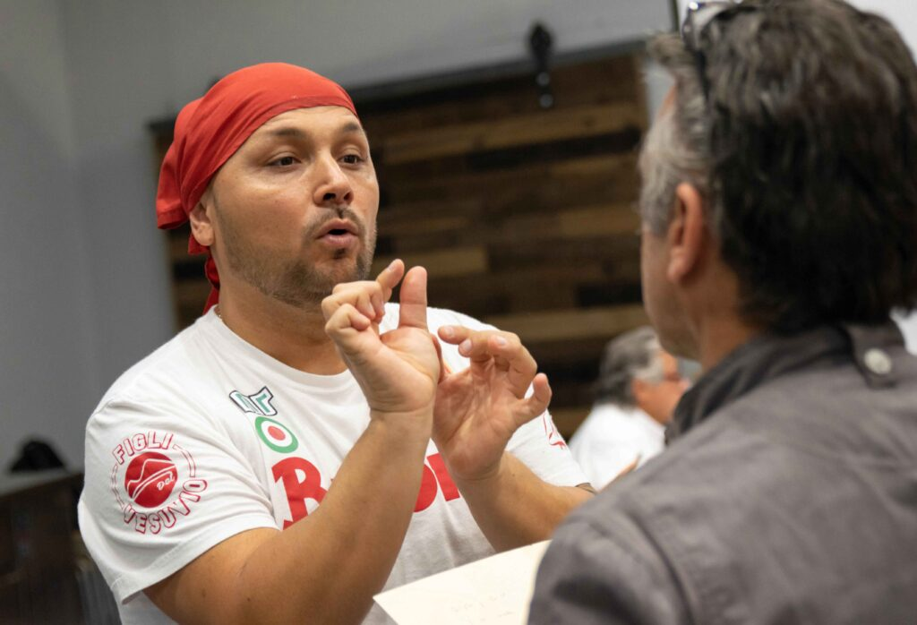 Chef Ciro Iovine wearing red headwear instructs students