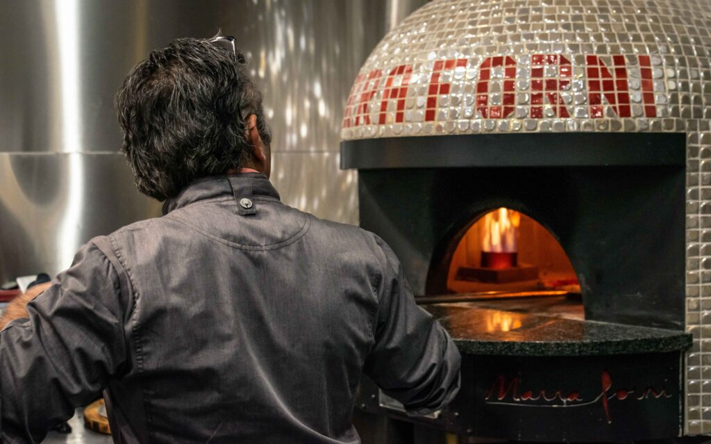 Man in grey Chefs Jacket spinning pizza in gas burning Marra Forni brick oven