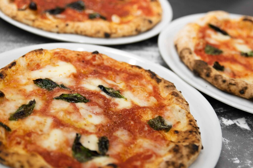 three neapolitan pizzas with melted mozzarella cheese and tomato sauce on white dinner plates