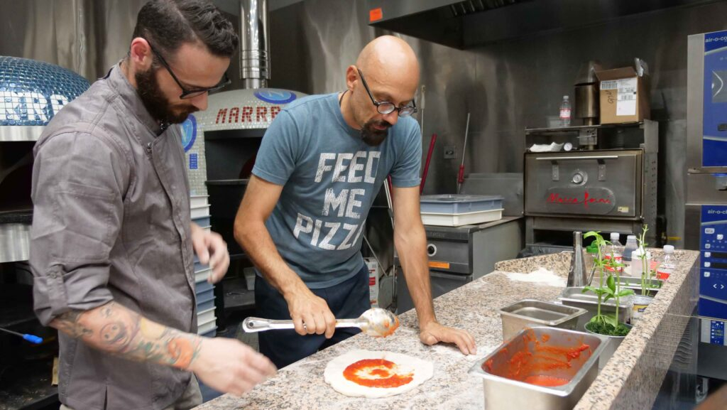 Chef Giulio Adriani wearing a blue shirt that says Feed Me Pizza holding spoon and teaching student how to spread tomato sauce on pizza dough