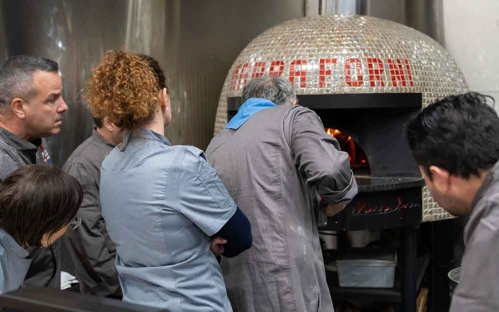 Students standing behind chef enzo coccia intently as they watch the master pizzaiolo operate a wood-fired oven