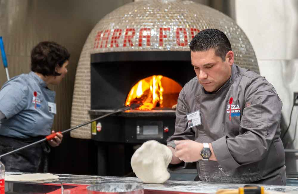Male chef slaps dough in front of a wood fired oven being watched by a female chef in the background
