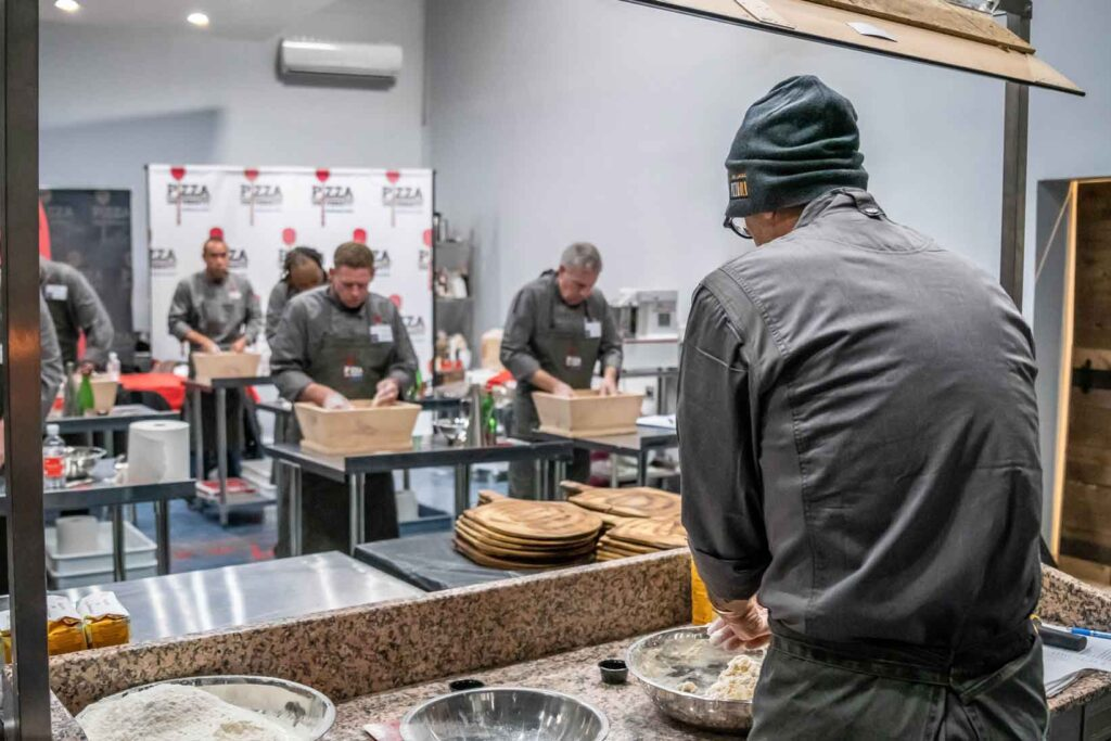 Chef instructor stands under mirror to teach students how to properly mix dough