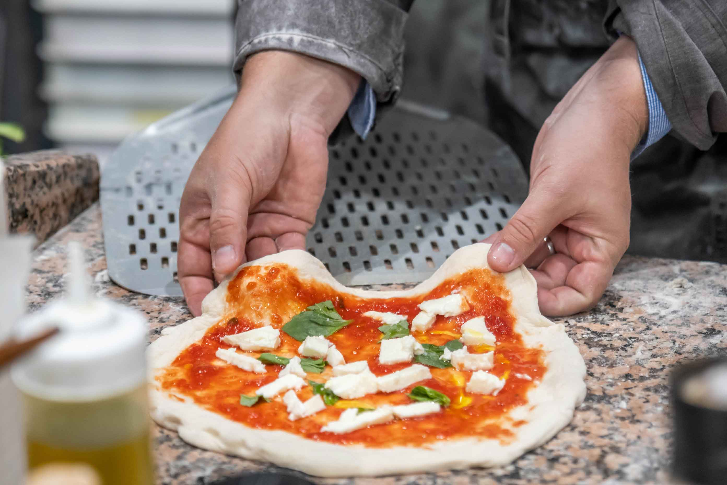 Female hands pull uncooked margherita pizza on a peel