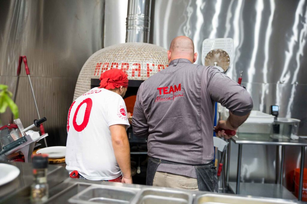 two chefs wearing team Marra Forni jackets at Pizza University operate a gold brick oven
