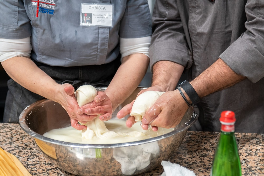 2 pairs of hands make fresh white mozzarella from bowl