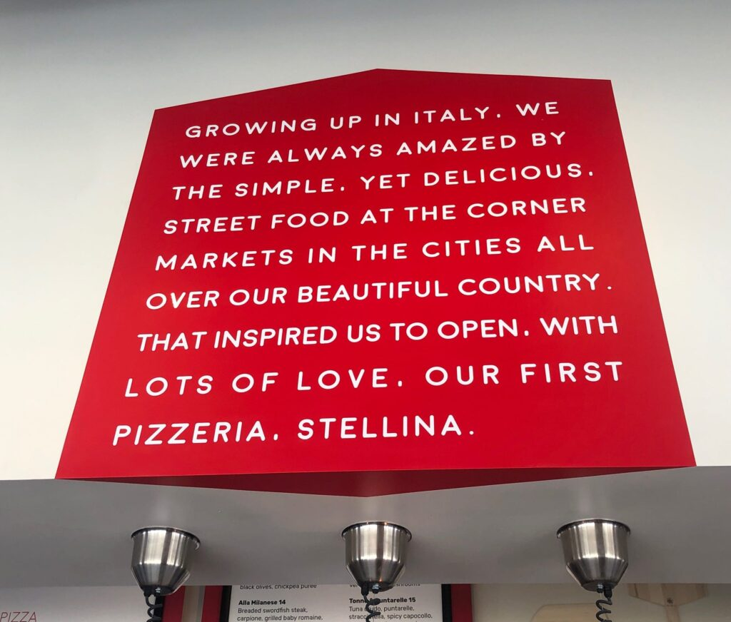 "Red Store Sign that says ""Our First Pizzeria. Stellina"""